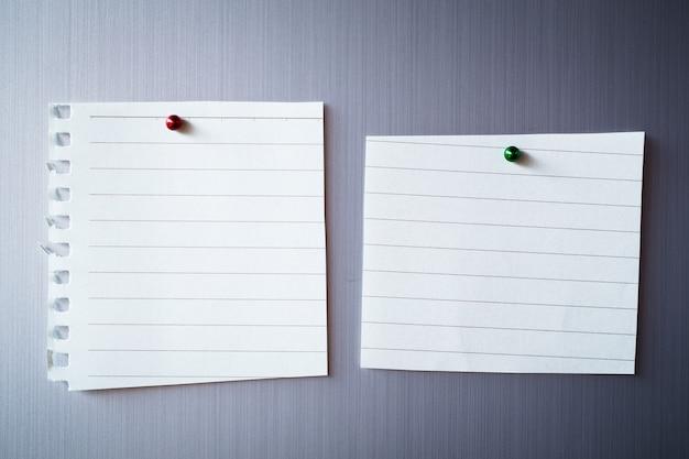 Pusty arkusz papieru na drzwiach lodówki. papierowa notatka z magnesem.