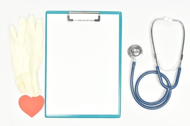 Pusty arkusz papieru na schowku i stetoskopie rękawice medyczne w kształcie serca na białym tle