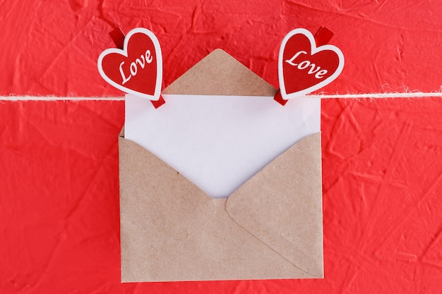 Pusty arkusz papieru w kopercie wisi na sznurku przymocowanym do bielizny w kształcie serca na czerwono na walentynki