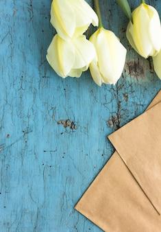 Pusty arkusz papieru z białych kwiatów tulipanów, widok z góry
