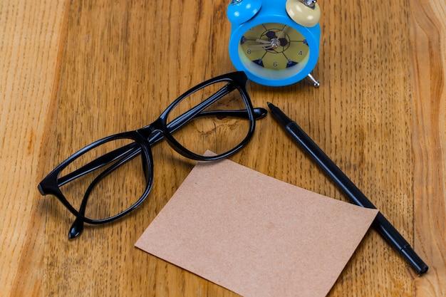 Pusty arkusz papieru z okularami, budzikiem i piórem na drewnianym stole.