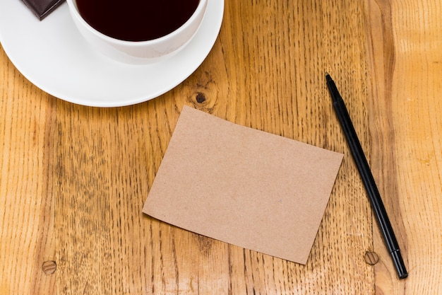 Pusty arkusz papieru z piórem i kawą i na drewnianym stole.