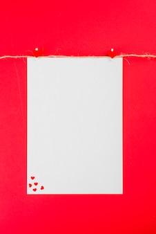 Pusty arkusz papieru z serca wisi na liny