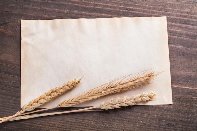 Pusty arkusz papieru z żyta pszenicy uszy na vintage deska