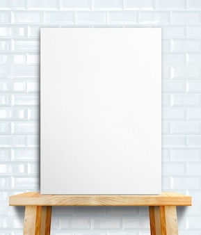 Pusty białego papieru plakat na drewno stole przy biel płytki ścianą
