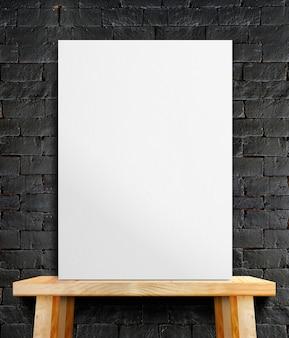 Pusty białego papieru plakat na drewno stole przy czarną kamienną ścianą