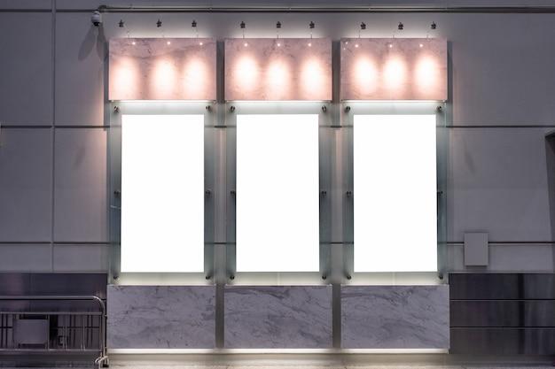 Pusty biały billboard z lampą świeci na ścianie
