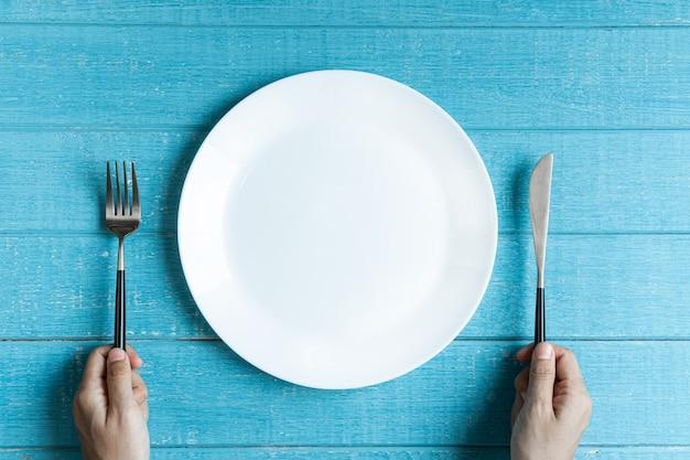 Pusty biały ceramiczny okrągły talerz, ręce trzymając nóż i widelec na niebieskim drewnianym stole.