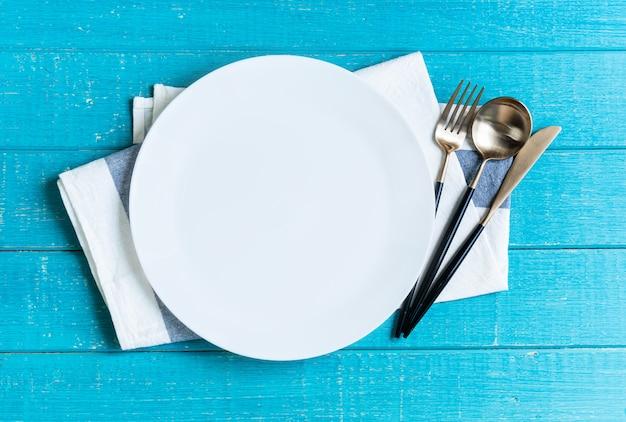 Pusty biały ceramiczny okrągły talerz z obrusem, nożem, łyżką i widelcem na niebieskim drewnianym stole.