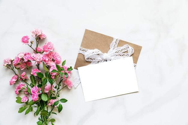 Pusty biały kartkę z życzeniami z bukietem różowych kwiatów róży na białym marmuru stole z miejsca kopiowania. widok z góry