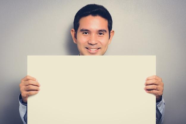 Pusty biały karton trzymający mężczyzna z uśmiechniętą twarzą