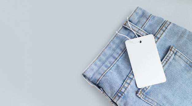Pusty biały kartonowy tag lub etykieta z liną na tle ubrania dżinsów