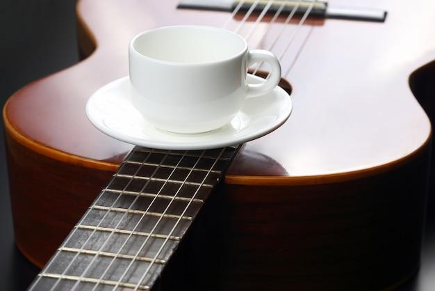 Pusty biały kubek leżący na gitarze akustycznej