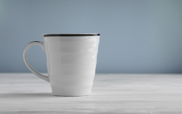 Pusty biały kubek próbny up na białym drewnianym stole i błękitnym tle