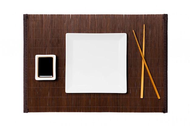 Pusty biały kwadratowy talerz z pałeczkami do sushi i sosu sojowego na ciemnej bambusowej macie