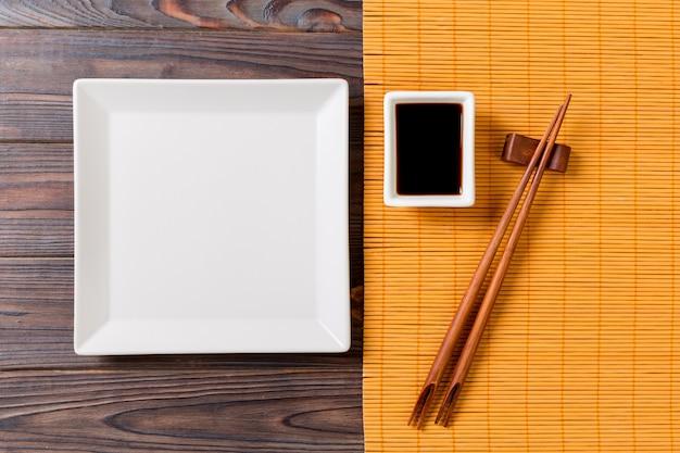 Pusty biały kwadratowy talerz z pałeczkami do sushi i sosu sojowego