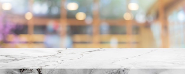 Pusty biały marmurowy blat z kamienia i rozmycie szklanego okna wnętrza kawiarni i restauracji