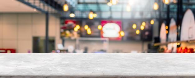 Pusty biały marmurowy blat z kamienia i rozmycie szklanej okna wewnętrznej kawiarni