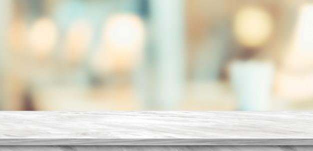 Pusty biały marmurowy stół i zamazany miękkiego światła stół w luksusowej restauraci