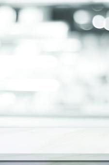 Pusty biały marmurowy stół nad sklepem rozmycia z jasnym tłem bokeh, baner, montaż wyświetlacza produktu