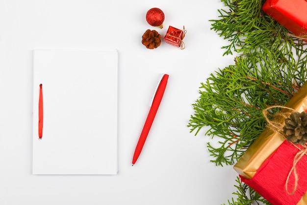 Pusty biały notatnik i czerwony długopis na boże narodzenie spacji. boże narodzenie gałęzie jodły, szyszki, prezenty. list do świętego mikołaja, makieta. pusty notatnik biały i czerwony długopis na białym tle.