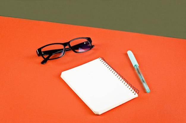 Pusty biały notatnik, okulary i długopis na pomarańczowym i zielonym tle. minimalistyczna koncepcja z miejscem na tekst. makieta z elementami wystroju.