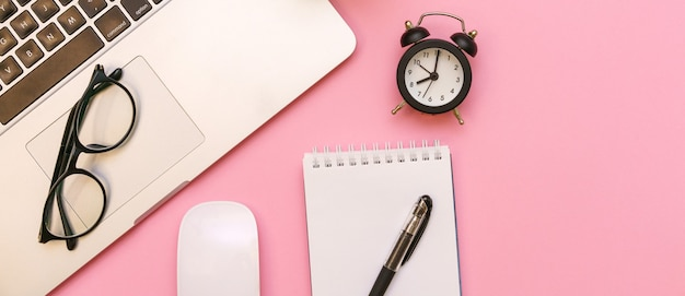 Pusty biały notatnik z akcesoriami biurowymi i osobistymi czarny budzik i okulary na różowym tle...