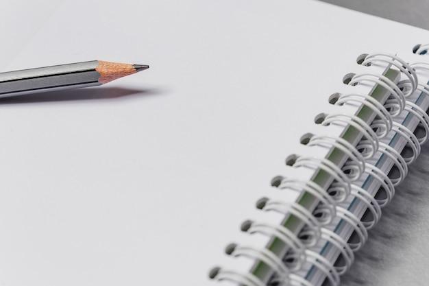 Pusty biały notatnik z bliska i szary ołówek