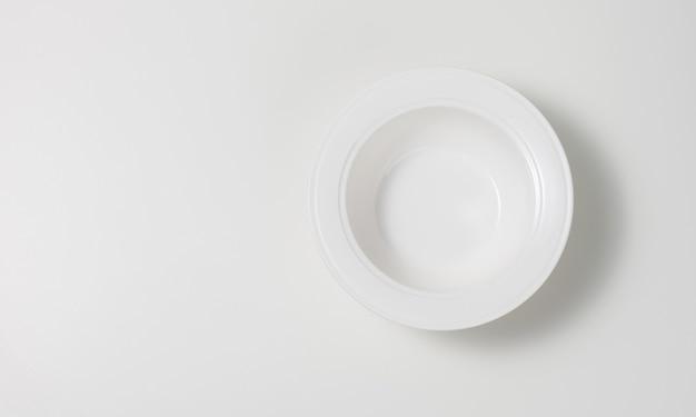 Pusty biały okrągły ceramiczny talerz do zupy na białym stole, widok z góry, kopia przestrzeń