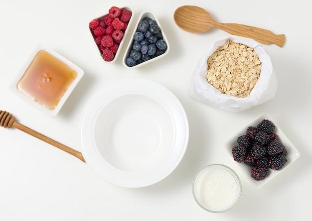 Pusty biały okrągły talerz ceramiczny, płatki owsiane i owoce do gotowania owsianki na białym stole, widok z góry