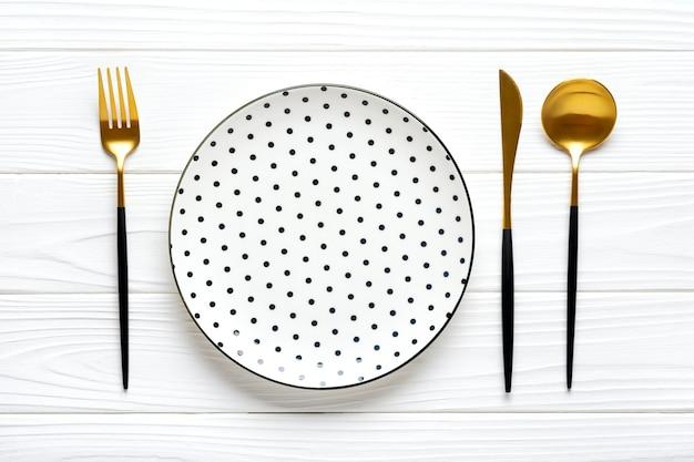 Pusty biały okrągły talerz z czarnym groszkiem i sztućcami na drewnianym stole