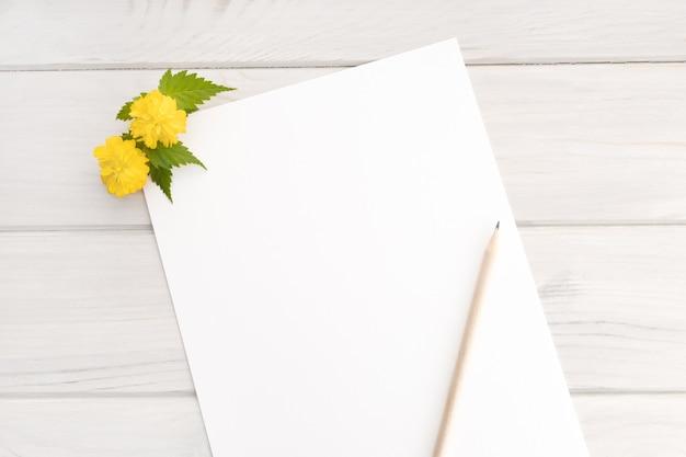 Pusty biały papier, gałąź żółtego kwiatu i ołówek na drewnianym stole