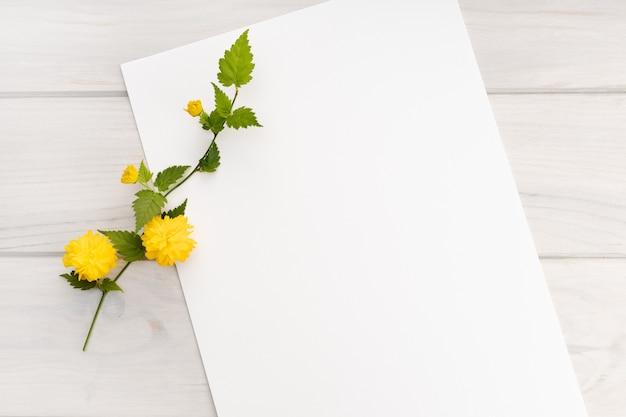 Pusty biały papier, gałąź żółty kwiat na drewnianym stole