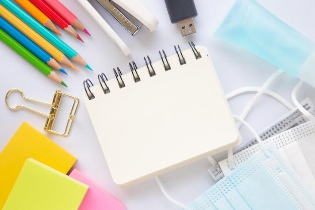 Pusty biały papier lub notatnik z stacjonarnym, maską i środkiem dezynfekującym do rąk na białym tle.
