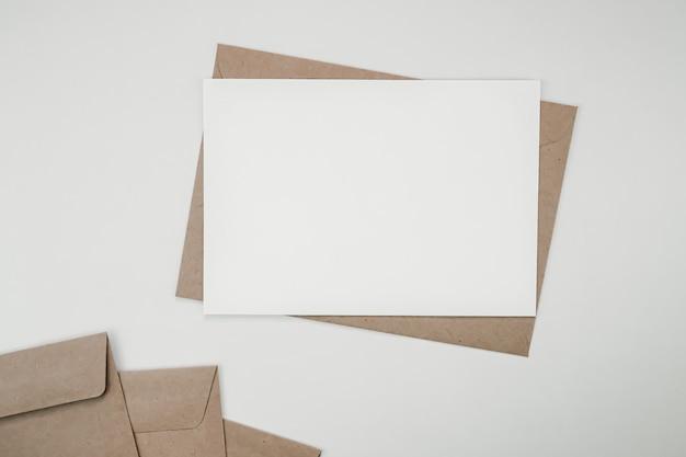 Pusty biały papier na brązowej kopercie papierowej. poziome puste karty z pozdrowieniami.