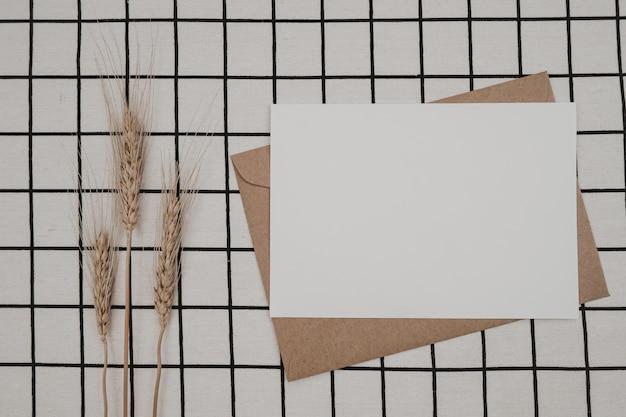 Pusty biały papier na brązowej kopercie papierowej z suchym kwiatem jęczmienia i pudełkiem kartonowym na białej tkaninie z czarnym wzorem siatki