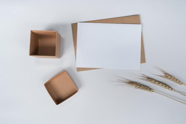 Pusty biały papier na brązowej kopercie papierowej z suchym kwiatem jęczmienia i pudełkiem kartonowym. widok z góry koperty craft na białym tle.