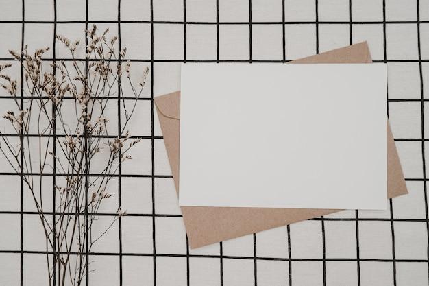 Pusty biały papier na brązowej kopercie papierowej z suchym kwiatem limonium i pudełkiem kartonowym na białej tkaninie z czarnym wzorem siatki. makieta poziomej pustej karty z pozdrowieniami.