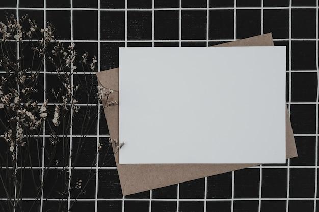 Pusty biały papier na brązowej kopercie papierowej z suchym kwiatem limonium i pudełkiem kartonowym na czarnej tkaninie z czarno białym wzorem siatki. makieta poziomej pustej karty z pozdrowieniami.