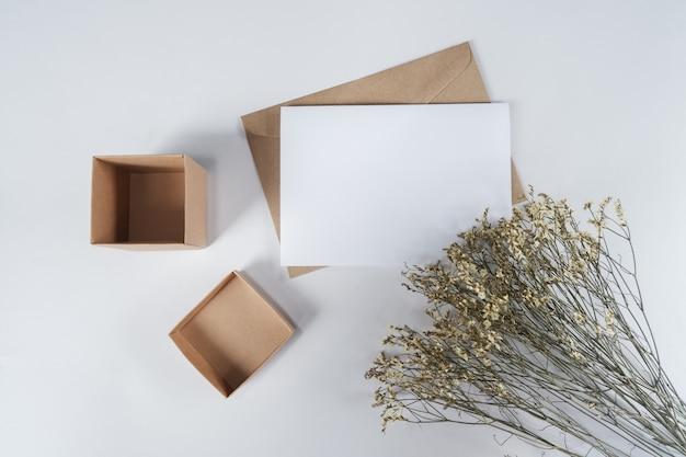 Pusty biały papier na brązowej kopercie papierowej z suchym kwiatem limonium i pudełkiem kartonowym. widok z góry koperty z papieru craft na białym tle.