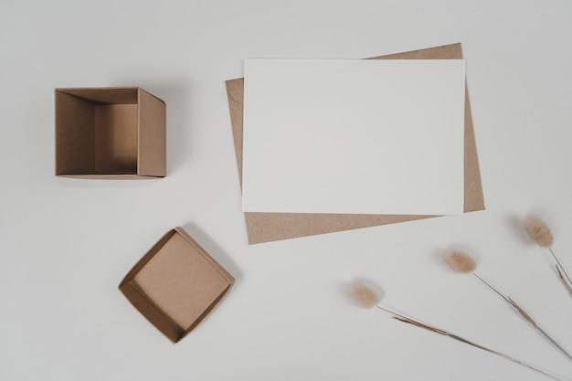 Pusty biały papier na brązowej kopercie papierowej z suchym kwiatem ogona królika i pudełkiem kartonowym. makieta poziomej pustej karty z pozdrowieniami. widok z góry koperty z papieru craft na białym tle.