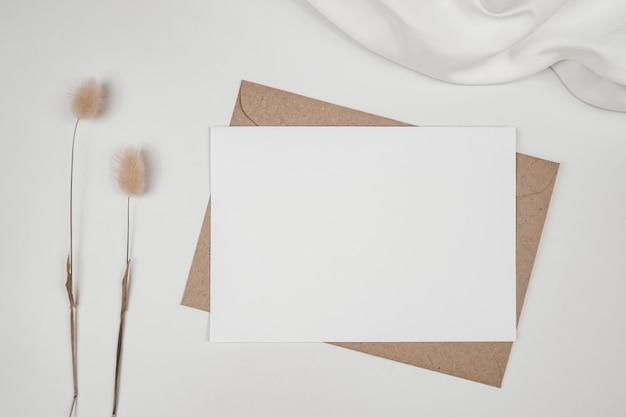 Pusty biały papier na brązowej kopercie papierowej z suchym kwiatem ogona królika na białej szmatce