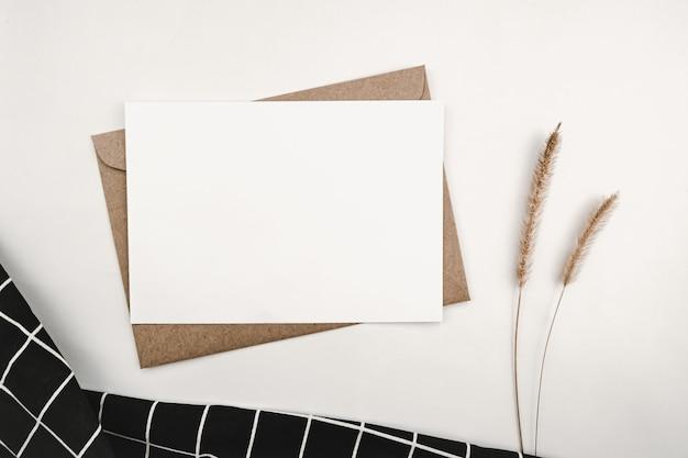 Pusty biały papier na brązowej kopercie papierowej z suchym kwiatem szczeciniastego wycinka i czarnym materiałem