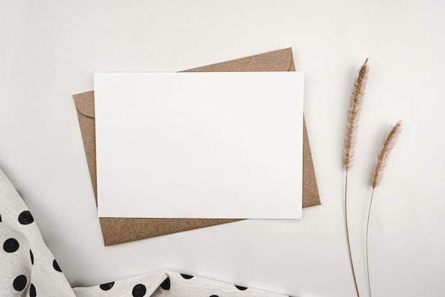 Pusty biały papier na brązowej kopercie papierowej z suchym kwiatem szczeciniastego wycinka i czarnymi kropkami z białej tkaniny