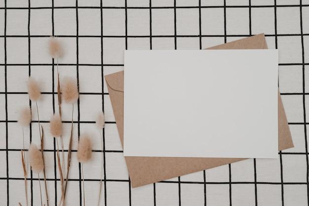 Pusty biały papier na brązowej kopercie papierowej z suchym kwiatem z ogona królika i pudełkiem kartonowym na czarnej tkaninie z czarno białym wzorem siatki. makieta poziomej pustej karty z pozdrowieniami.