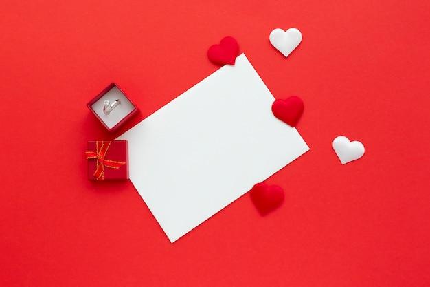 Pusty biały papier na czerwonym tle z sercami i pierścionkiem w pudełku. tło valentine's day. makieta listu miłosnego. płasko, widok z góry.
