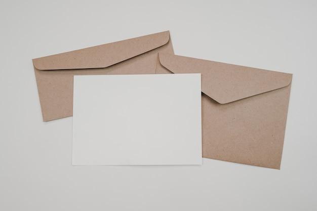 Pusty biały papier na dwóch brązowych kopertach. makieta poziomej pustej karty z pozdrowieniami. widok z góry koperty z papieru craft na białym tle. płaskie ułożenie papeterii.