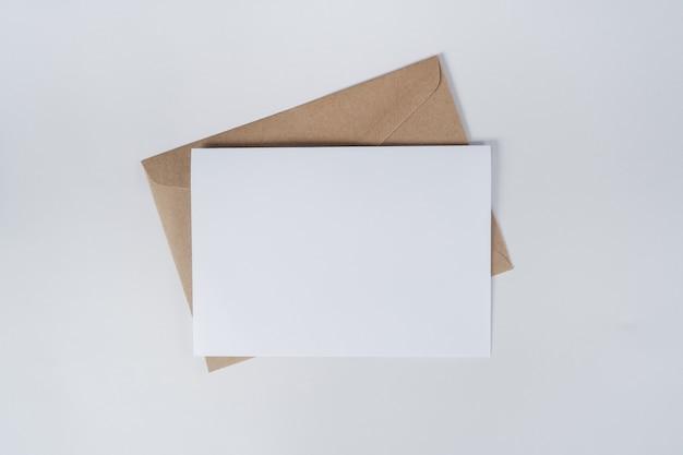Pusty biały papier na kopercie z brązowego papieru. widok z góry koperty z papieru craft na białym tle. płaskie ułożenie papeterii.