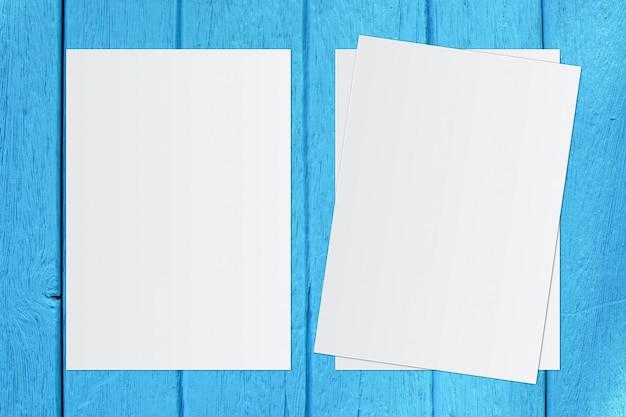 Pusty biały papier na niebieskim drewnianym tle wprowadzania tekstu.