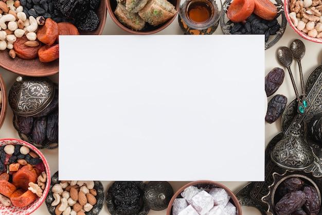 Pusty biały papier nad tradycyjnymi słodyczami i orzechami dla ramadanu